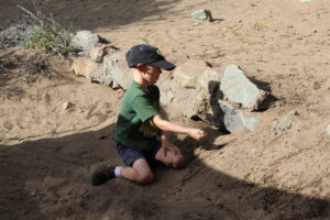child building his own sand dunes