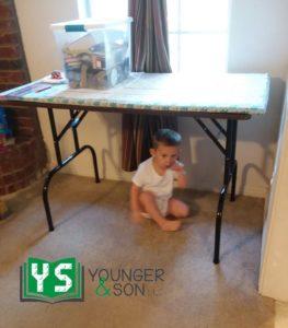small boy hiding under a table